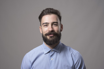 Horizontal  head and shoulder portrait of young bearded business man smiling at camera against gray studio background.