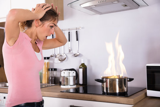 Shocked Young Woman Looking At Cooking Pot On Fire
