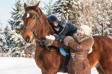 Small girl and mom near horse in a winter