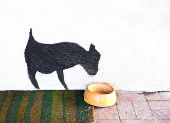An eine Wand gesprühte Silhouette eines Hundes mit Futternapf und Fußmatte