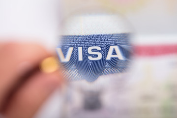 Human Hand Zooming At Visa Text