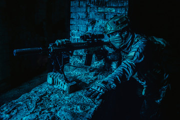 Marksman in action in the ruined city under cover of darkness