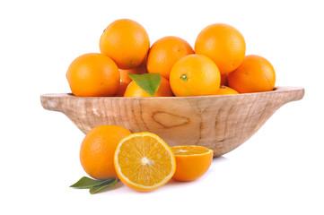 orange in wooden bowl and sliced orange on wite background