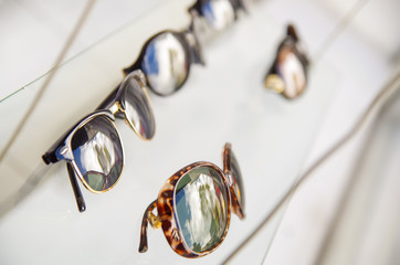 Close up of assorted beautiful glasses in optician store inside of showcase, in a blurred background