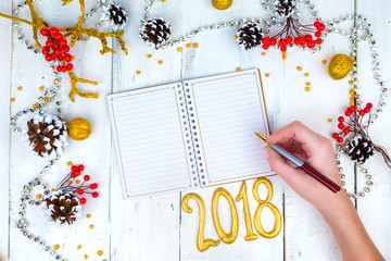 Christmas wooden background with cones and notepad. The hands that write in the notebook.