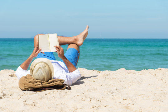 A handsome man relaxing on a book reading on the beach.