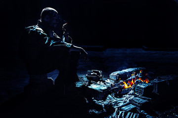 Special forces soldier after the fight sitting by the fire in ruined building smoking cigarette