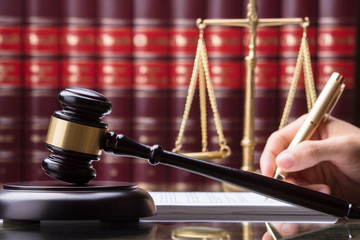Gavel In Front Of Person Writing On Document