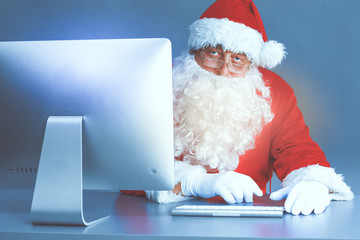 Santa Claus reading children letters and writing responses to them using laptop