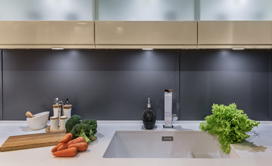 Modern kitchen in high-tech style with sliding doors instead of apron. Fresh salad, carrots, cabbage Broccoli lie on the countertop next to the sink.