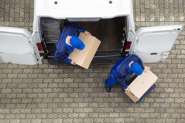 Two Delivery Men Unloading Cardboard Box From Truck