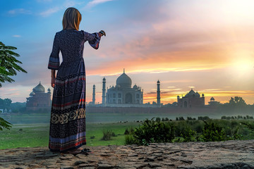 Beautiful girl points to Taj Mahal. Travel concept Fototapete