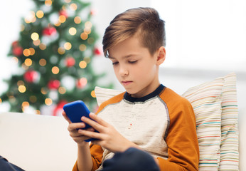 boy with smartphone at home at christmas