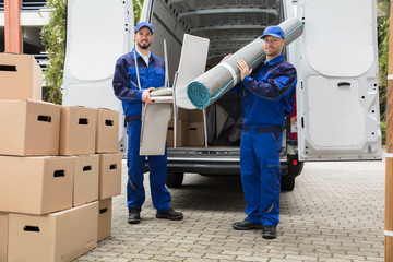Two Delivery Men Holding Chairs And Carpet