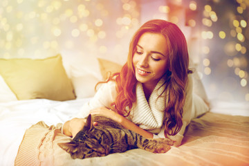 Fototapete - happy young woman with cat lying in bed at home