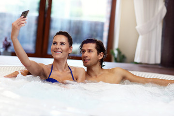 Happy couple enjoying jacuzzi in hotel spa