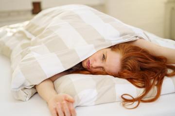 frau liegt im bett und schaut verschlafen unter der bettdecke hervor