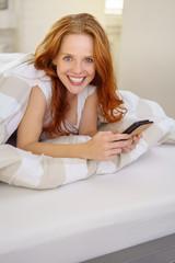 frau liegt im bett und hält ihr smartphone in der hand