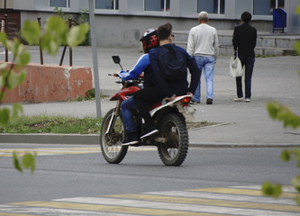 a motorcyclist with a passenger without a helmet