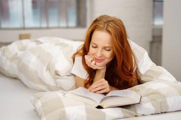 entspannte frau liegt im bett und liest ein buch