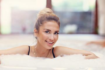 Happy woman enjoying jacuzzi in hotel spa