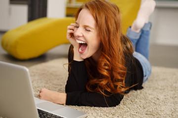 frau liegt auf dem fußboden im wohnzimmer und schaut lachend auf ihren laptop
