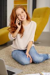 frau sitzt zuhause auf dem teppich und telefoniert