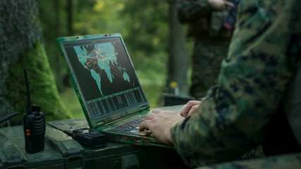 Military Operation in Action, Soldiers Using Military Grade Laptop Targeting Enemy with Satellite. In the Background Camouflaged Tent on the Forest.