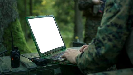 Close-up Soldier Uses Military Grade Laptop with White/Green Screen. In the Background Camouflaged Army Base in the Forest.
