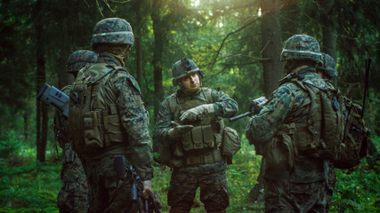 Squad Leader Discusses Military Operation Details with Soldiers, Commander Gives Orders. Fully Equipped and Armed Soldiers Ready for Mission in a Dense Forest.