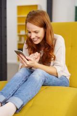 frau sitzt zuhause auf einem gelben sessel und schaut auf ihr handy