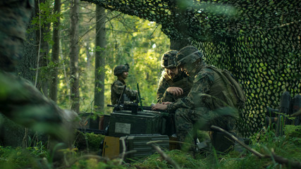 Military Staging Base, Officer Gives Orders to Signalman, They Use Radio and Army Grade Laptop. They're in Camouflaged Tent in a Forest. They're on Reconnaissance Operation/ Mission.