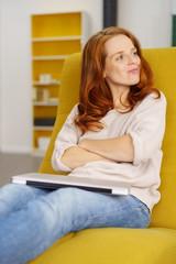 zufriedene frau sitzt zuhause in ihrem sessel