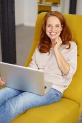 frau sitzt entspannt zuhause und surft im internet
