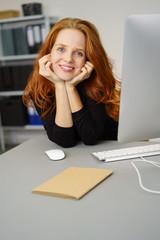 lächelnde frau sitzt am schreibtisch im büro und stützt den kopf auf