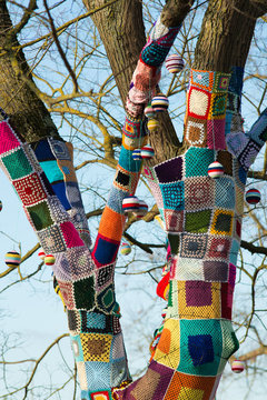 knitted woollen yarn bomb tree with baubles and blue sky background