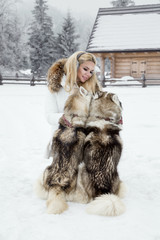 Beautiful blonde woman, standing on snow and holding Husky dogs. In the background is a beautiful view of mountains and snow.
