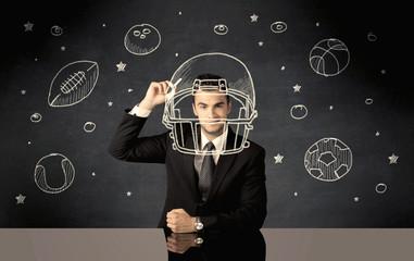 Businessman drawing helmet and sport balls