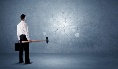 Business man hitting wall with a hammer