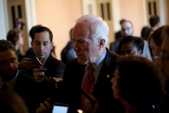 U.S. Senate Majority Whip John Cornyn (R-TX) speaks to reporters on his way to the Senate floor during debate over the Republican tax reform plan in Washington