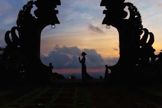 Silhouette of woman full length at the balinese traditional gates at the top of Pura Besakih at sunset.