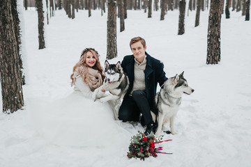 Cheerful couple are playing with siberian husky in snowy forest. Winter wedding Artwork