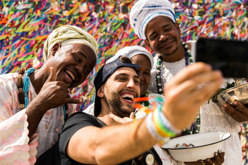 Tourist taking selfie photos with the locals in Salvador, Bahia, Brazil