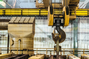 Steel hook of overhead crane over industrial equipment