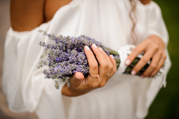 Girl in white dress holding in hands a bouquet of lavender
