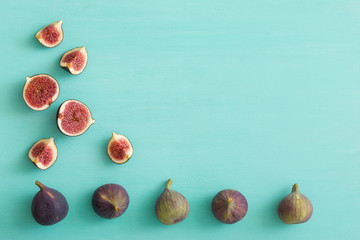 Top view on sliced and full fresh figs on turquoise wooden table or background. Healthy snack and food.