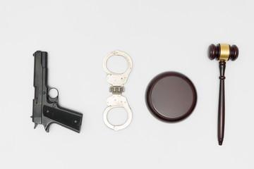 Judge gavel, handgun and handcuffs on white background