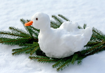 Christmas goose made of snow on fir branch