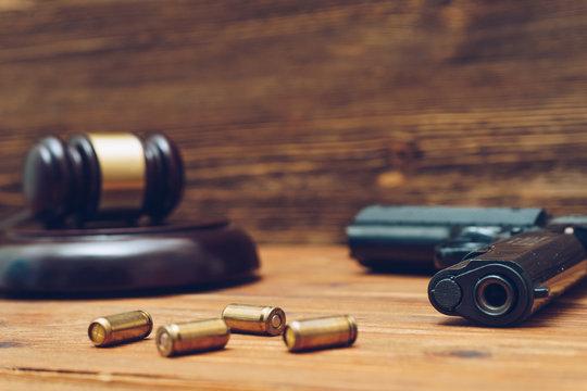 Judge gavel, handgun ανδ bullets on wooden background