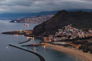 Dusk view of beautifully lit San Andres town with the capital city Santa Cruz de Tenerife in the background, Las Teresitas beach in the foreground and the North Atlantic Ocean to the left